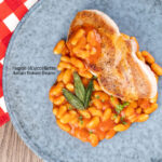 Portrait overhead image of Fagioli all'uccelletto or Italian Baked Beans served with a pork loin steak and crispy fried sage leaves featuring a title overlay