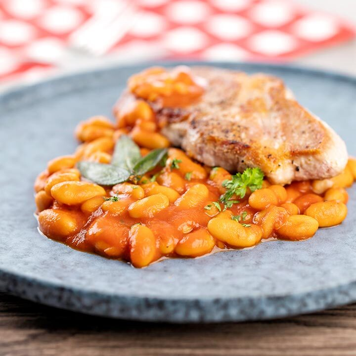 Square image of Fagioli all'uccelletto or Italian Baked Beans served with a pork loin steak and crispy fried sage leaves