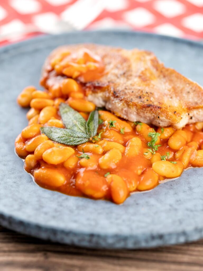 Portrait image of Fagioli all'uccelletto or Italian Baked Beans served with a pork loin steak and crispy fried sage leaves