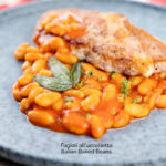 Portrait image of Fagioli all'uccelletto or Italian Baked Beans served with a pork loin steak and crispy fried sage leaves featuring a title overlay