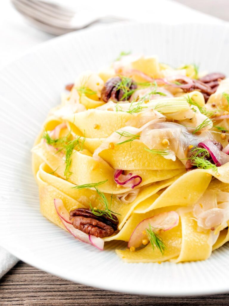 Portrait image of fennel pasta made with pappardelle served with pecan nuts and red onion served in a white pasta bowl