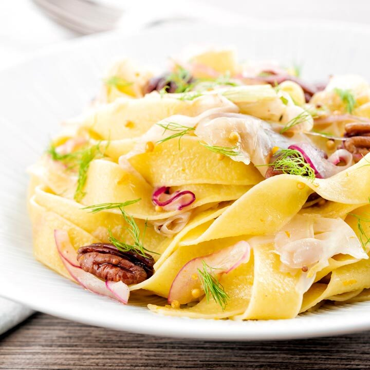 Square image of fennel pasta made with pappardelle served with pecan nuts and red onion served in a white pasta bowl