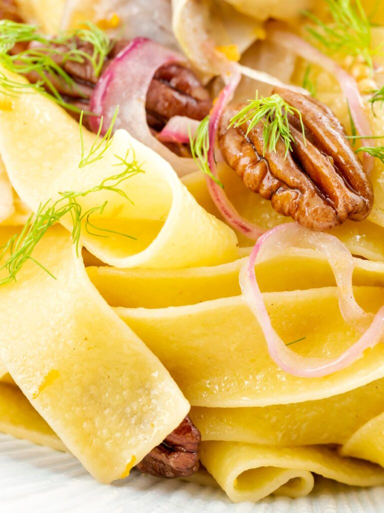 Portrait close up image of fennel pasta made with pappardelle served with pecan nuts and red onion served in a white pasta bowl