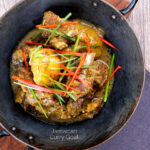 Portrait overhead image of Jamaican curry goat with potatoes served with shredded chilli and green onions served in an iron bowl featuring a title overlay