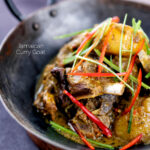 Portrait image of Jamaican curry goat with potatoes served with shredded chilli and green onions served in an iron bowl featuring a title overlay