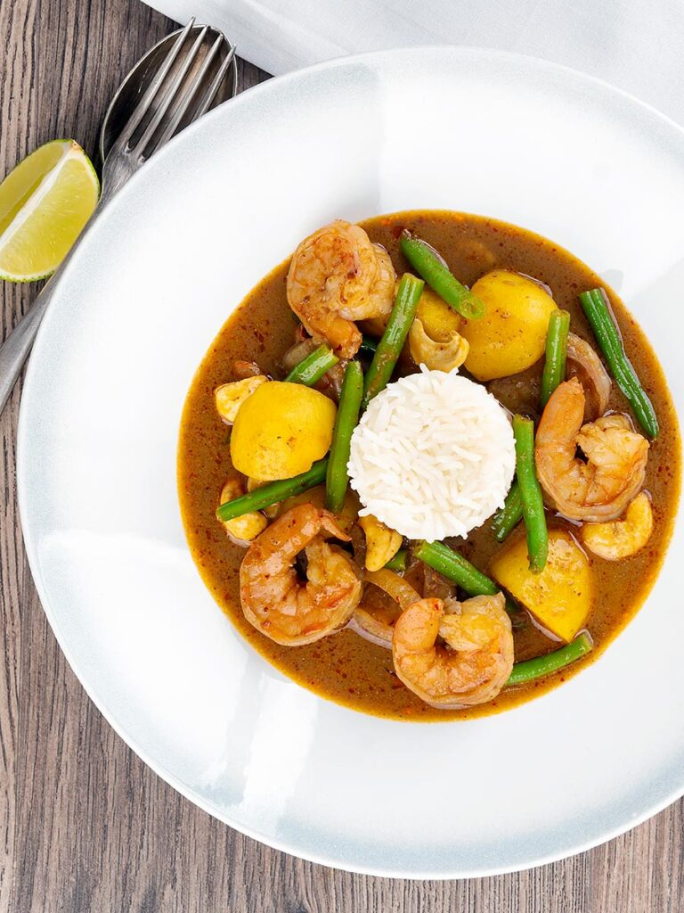 Portrait overhead image of a Thai Prawn Massaman Curry with potatoes and green beans served in a white bowl