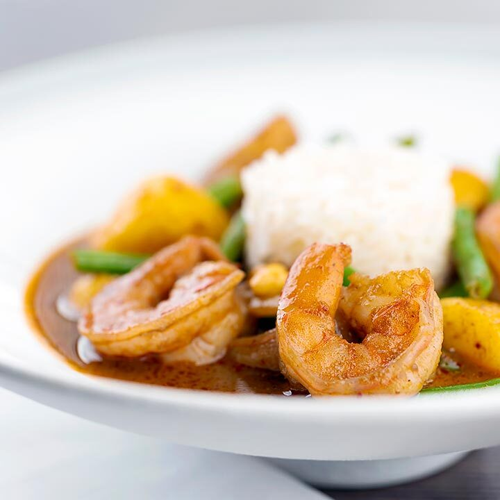 Square image of a Thai Prawn Massaman Curry with potatoes and green beans served in a white bowl