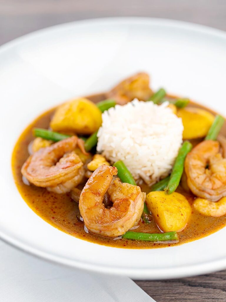 Portrait image of a Thai Prawn Massaman Curry with potatoes and green beans served in a white bowl