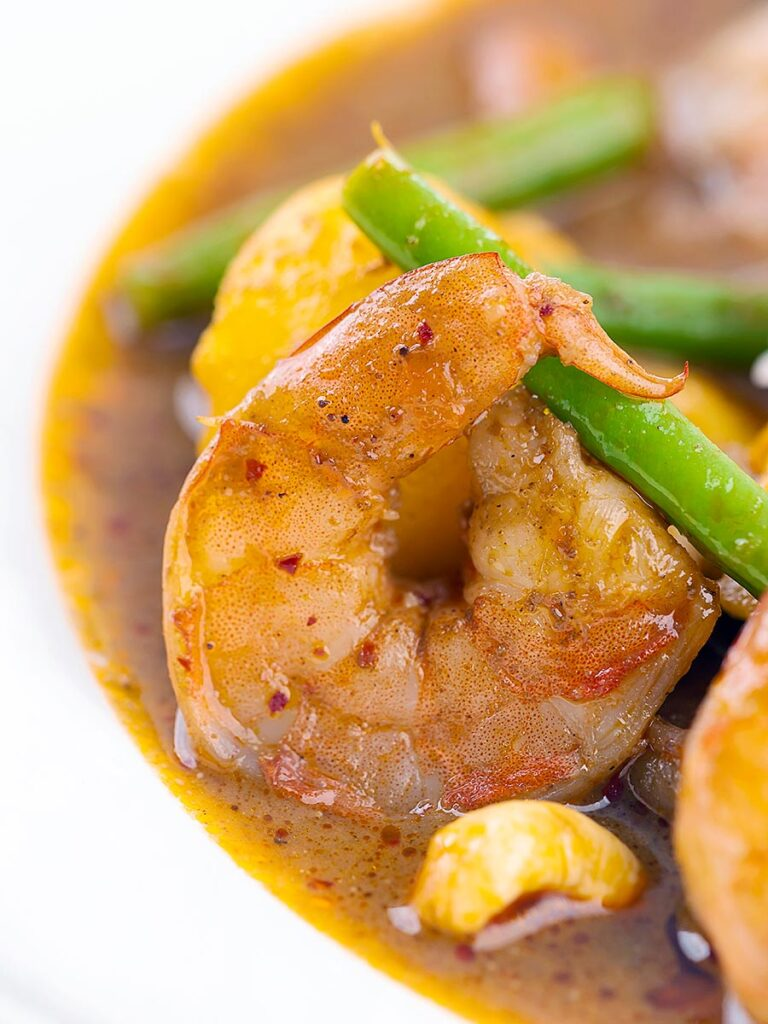 Portrait close up image of a Thai Prawn Massaman Curry with potatoes and green beans served in a white bowl