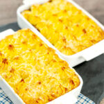 Portrait image of individual vegetarian shepherds pies or shepherdess pies served in white gratin dishes featuring a title overlay
