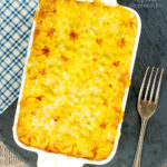 Portrait overhead image of a vegetarian shepherds pie or shepherdess pie served in a white gratin dish featuring a title overlay
