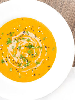 Portrait overhead image of a spicy carrot and lentil soup spiced with harissa paste and garnished with a swirl of tahini served in a white bowl