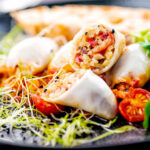 Portrait image of brown rice stuffed squid on a tomato sauce served with ciabatta bread and sprouted onion seeds featuring a title overlay
