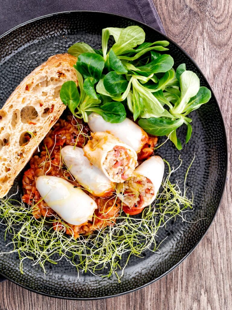 Square overhead image of brown rice stuffed squid on a tomato sauce served with ciabatta bread, lambs lettuce and sprouted onion seeds