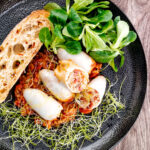 Portrait overhead image of brown rice stuffed squid on a tomato sauce served with ciabatta bread, lambs lettuce and sprouted onion seeds featuring a title overlay