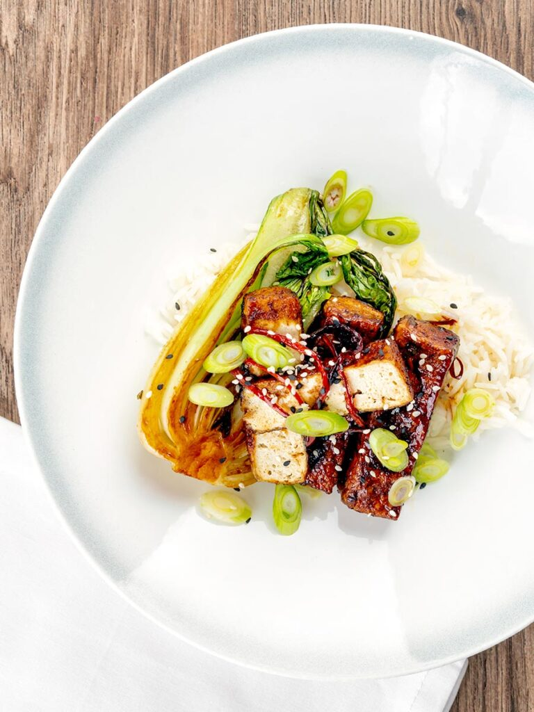Portrait overhead image of teriyaki tofu served with pak choi, white rice and spring onions on a white plate