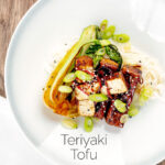 Portrait overhead image of teriyaki tofu served with pak choi, white rice and spring onions on a white plate featuring a title overlay