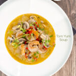 Portrait overhead image of a Thai Prawn Tom Yom Soup served in a white soup bowl featuring a title overlay