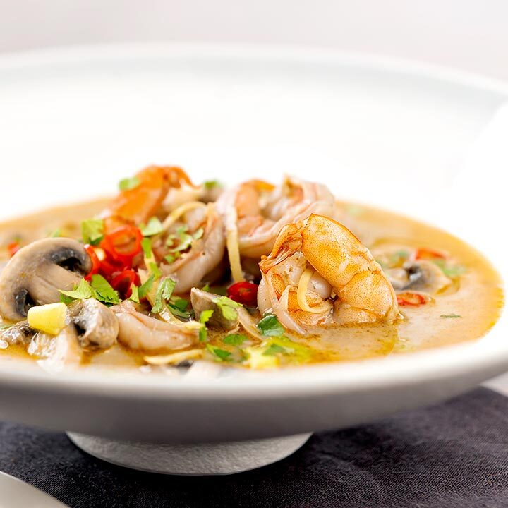 Square image of a Thai Prawn Tom Yom Soup served in a white soup bowl