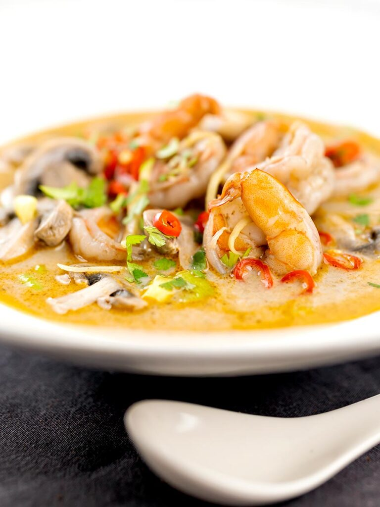 Portrait image of a Thai Prawn Tom Yom Soup served in a white soup bowl