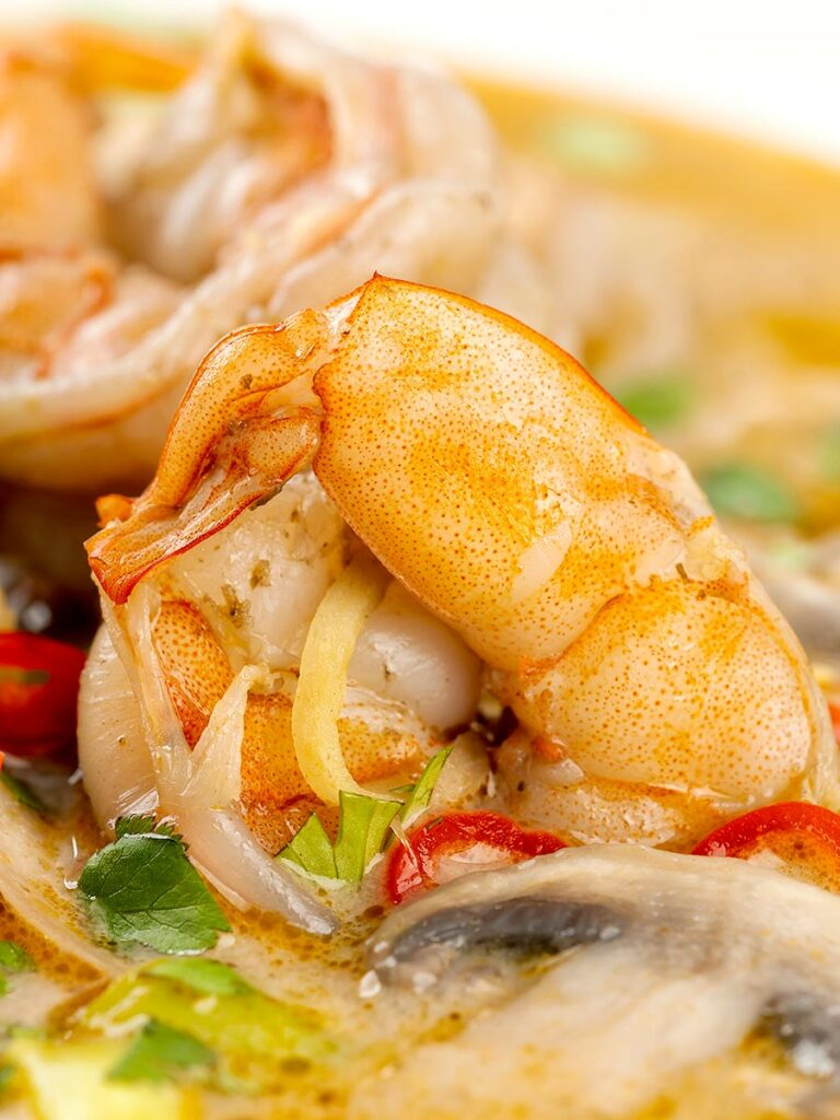Portrait close up image of a Thai Prawn Tom Yom Soup served in a white soup bowl