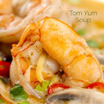 Portrait close up image of a Thai Prawn Tom Yom Soup served in a white soup bowl featuring a title overlay