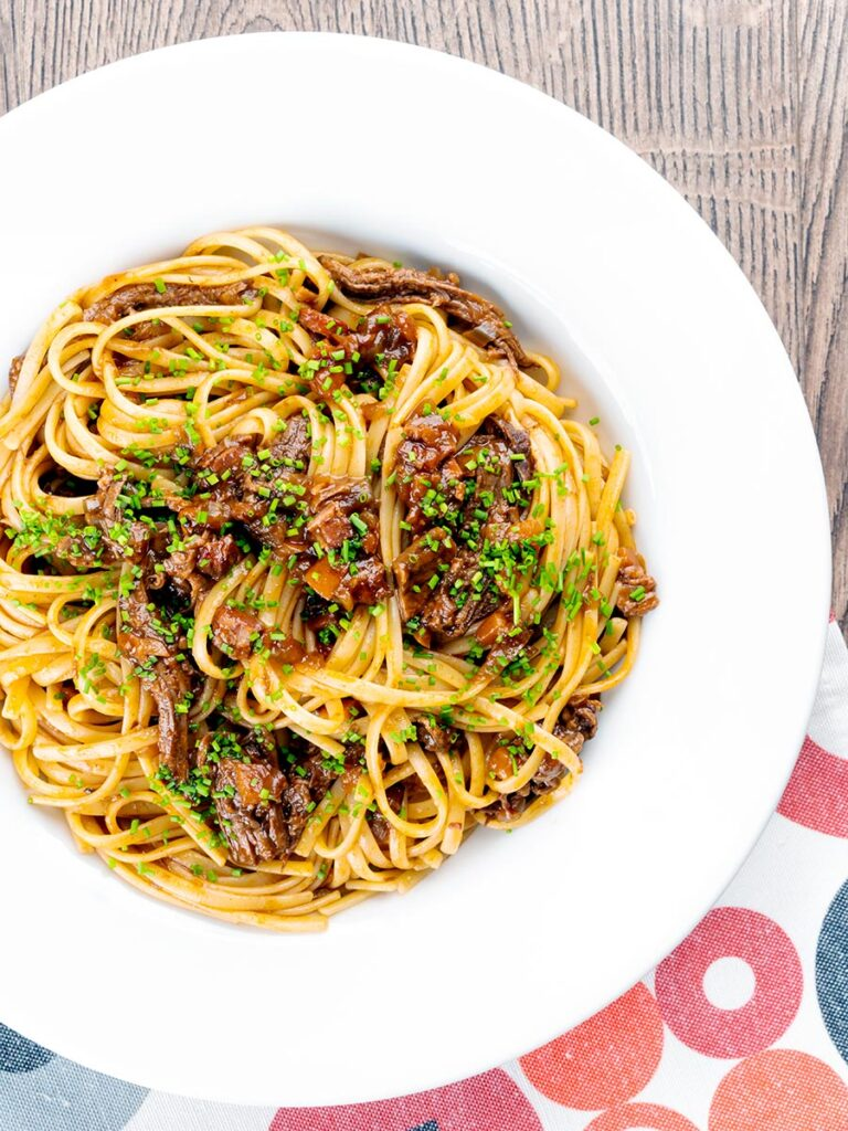 Portrait overhead image of a venison ragu served with linguini pasta garnished with snipped chives
