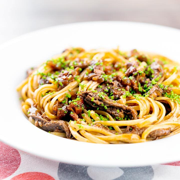 Square image of a venison ragu served with linguini pasta garnished with snipped chives