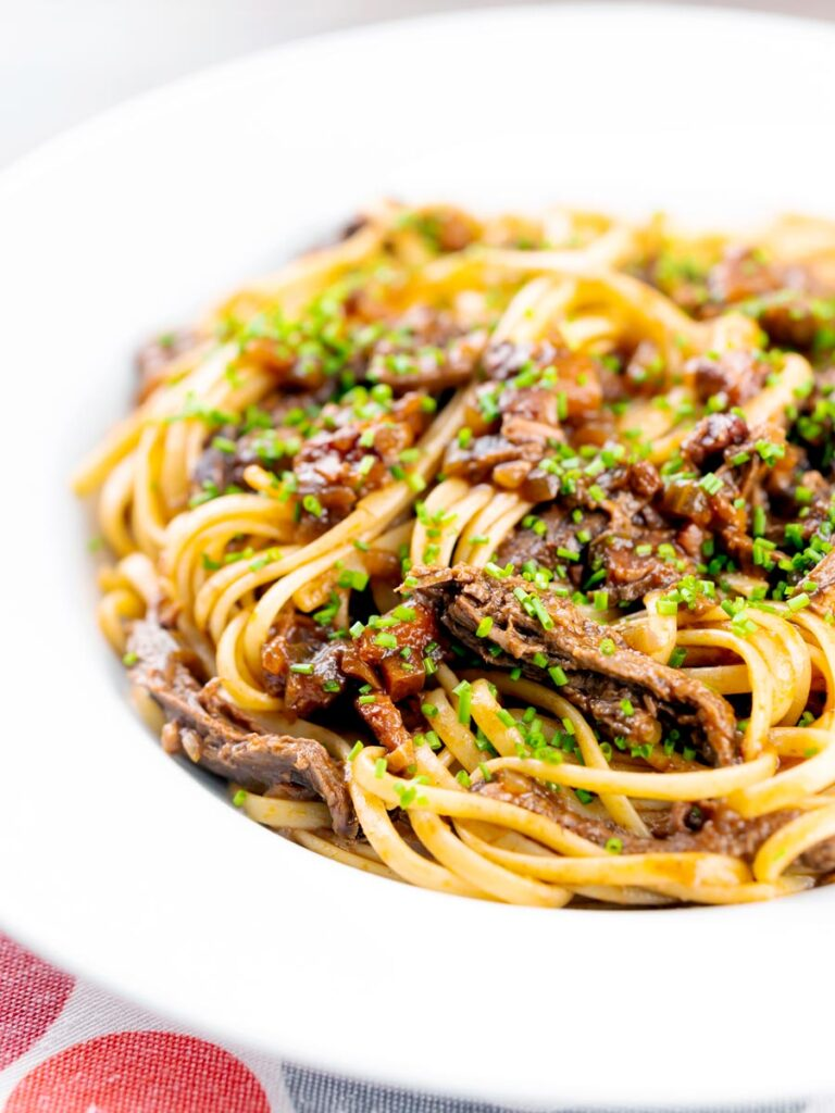 Portrait image of a venison ragu served with linguini pasta garnished with snipped chives and served in a white bowl