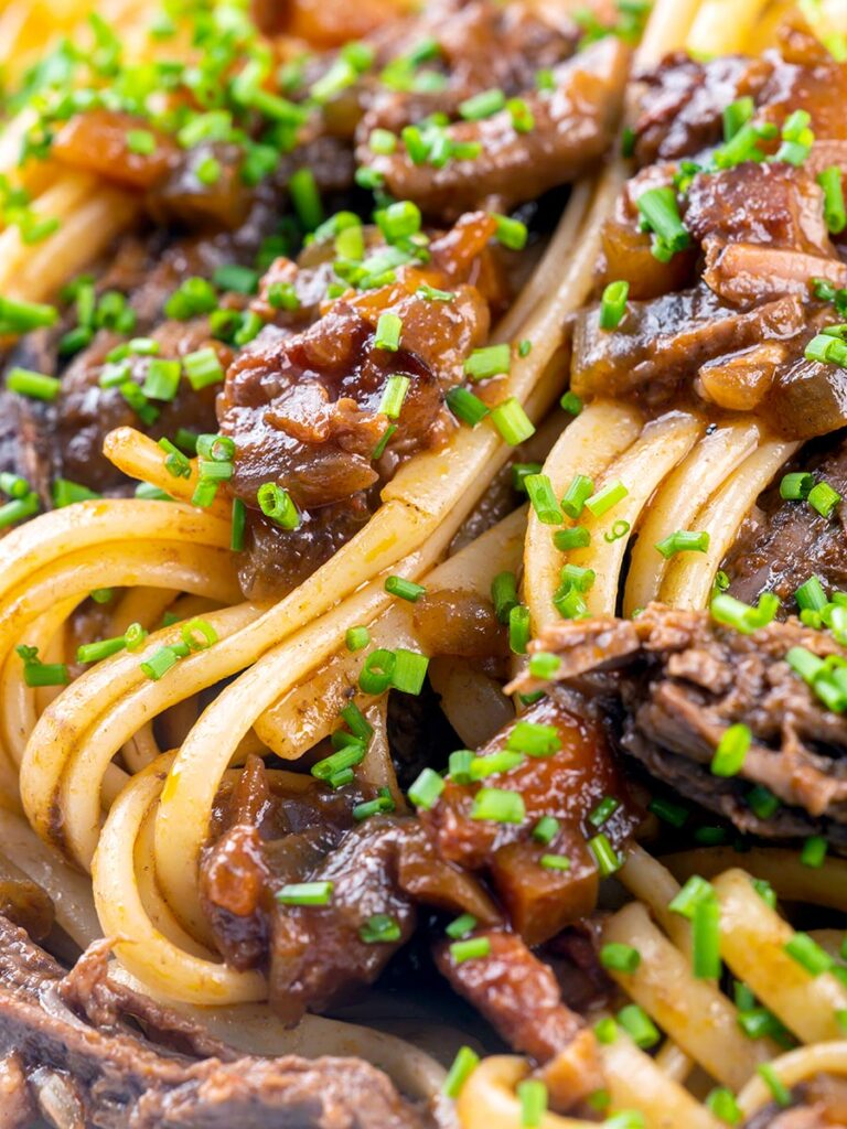 Portrait close up image of a venison ragu served with linguini pasta garnished with snipped chives.