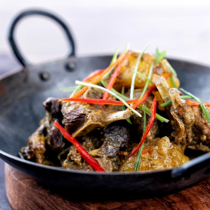 Square image of Jamaican curry goat with potatoes served with shredded chilli and green onions in an iron bowl