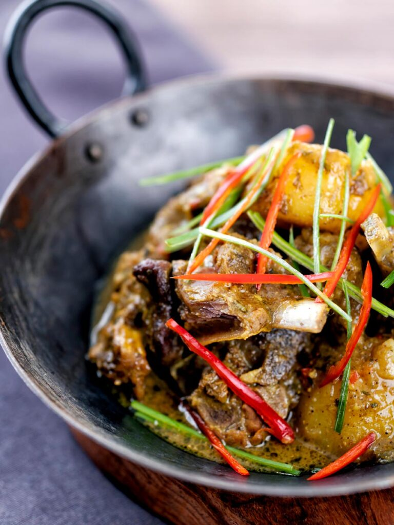 Portrait image of Jamaican curry goat with potatoes served with shredded chilli and green onions served in an iron bowl