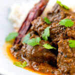 Portrait close up image of an achar gosht lamb or mutton curry served on a white plate with whole chilies and coriander leaves featuring a text overlay