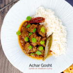 Portrait overhead image of an achar gosht curry served on a white plate with whole chilies, basmati rice and a naan bread featuring a text overlay