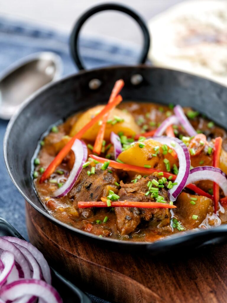 Portrait image of aloo gosht, an Indian lamb or mutton and potato curry served with naan bread and sliced red onions