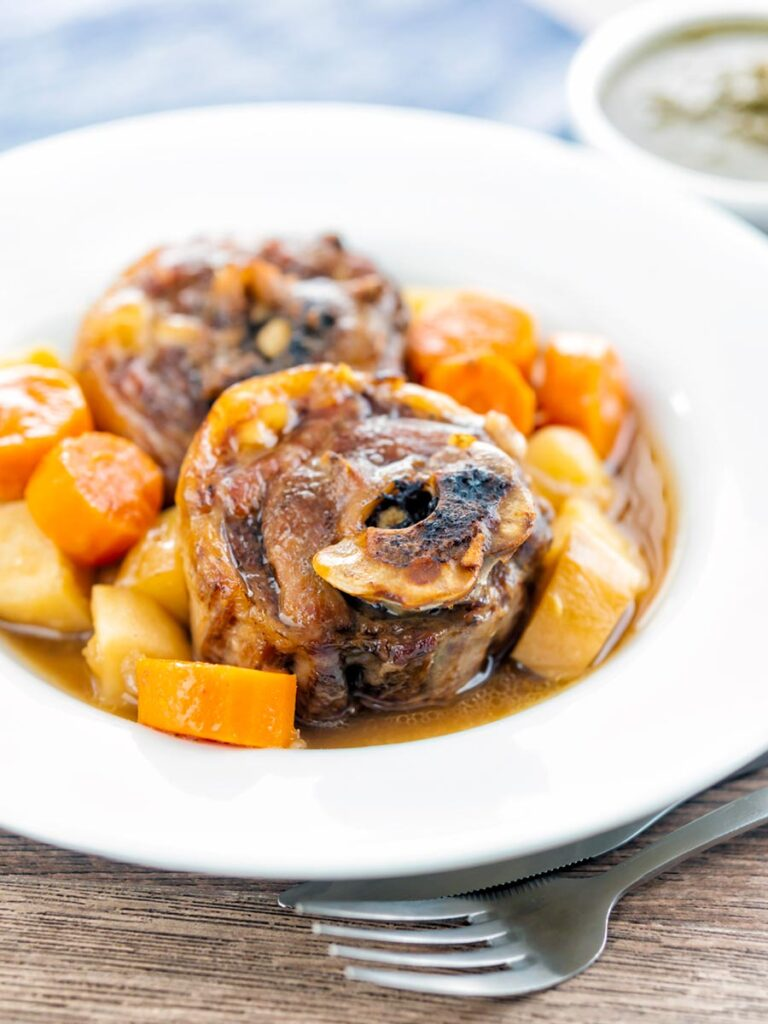 Portrait image of a lamb neck stew using bone in lamb neck chops, potatoes, carrots and parsnips served in a white bowl