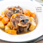 Portrait image of a lamb neck stew using bone in lamb neck chops, potatoes, carrots and parsnips served in a white bowl featuring a text overlay