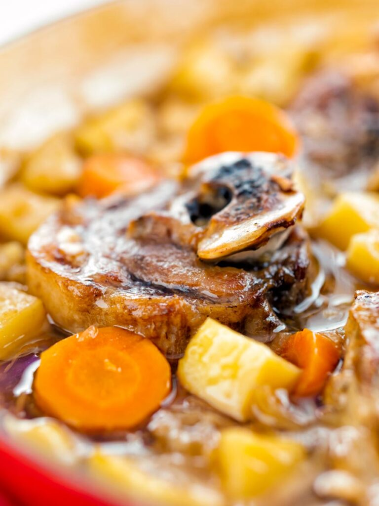 Portrait close up image of a lamb neck stew using bone in lamb neck chops, potatoes, carrots and parsnips