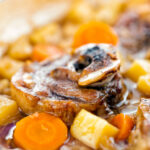 Portrait close up image of a lamb neck stew using bone in lamb neck chops, potatoes, carrots and parsnips featuring a title overlay
