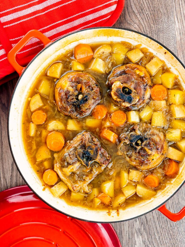 Portrait overhead image of a lamb neck stew using bone in lamb neck chops, potatoes, carrots and parsnips cooked in a red cast iron pan