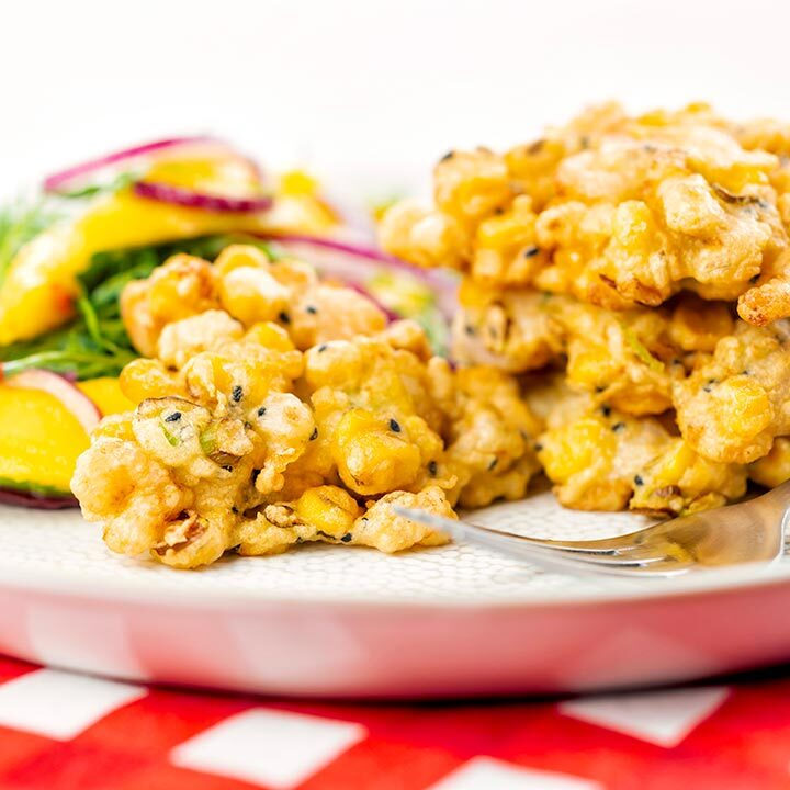 Square image of prawn fritters with sweetcorn and spring onion served with a mango salad