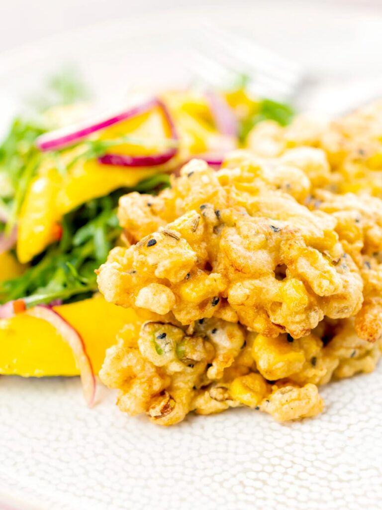 Portrait image of prawn fritters with sweetcorn and spring onion served with a mango salad