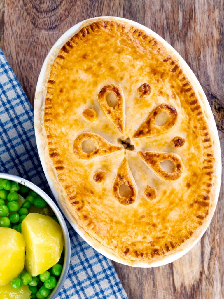 Portrait overhead image of a rabbit pie under a suet crust lid served along side a pan of buttered potatoes and peas.