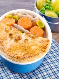 Portrait image of a rabbit pie under a suet crust lid with half removed to show the filling served alongside a pan of buttered potatoes and peas