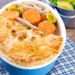 Portrait image of a rabbit pie under a suet crust lid with half removed to show the filling served alongside a pan of buttered potatoes and peas featuring a title overlay