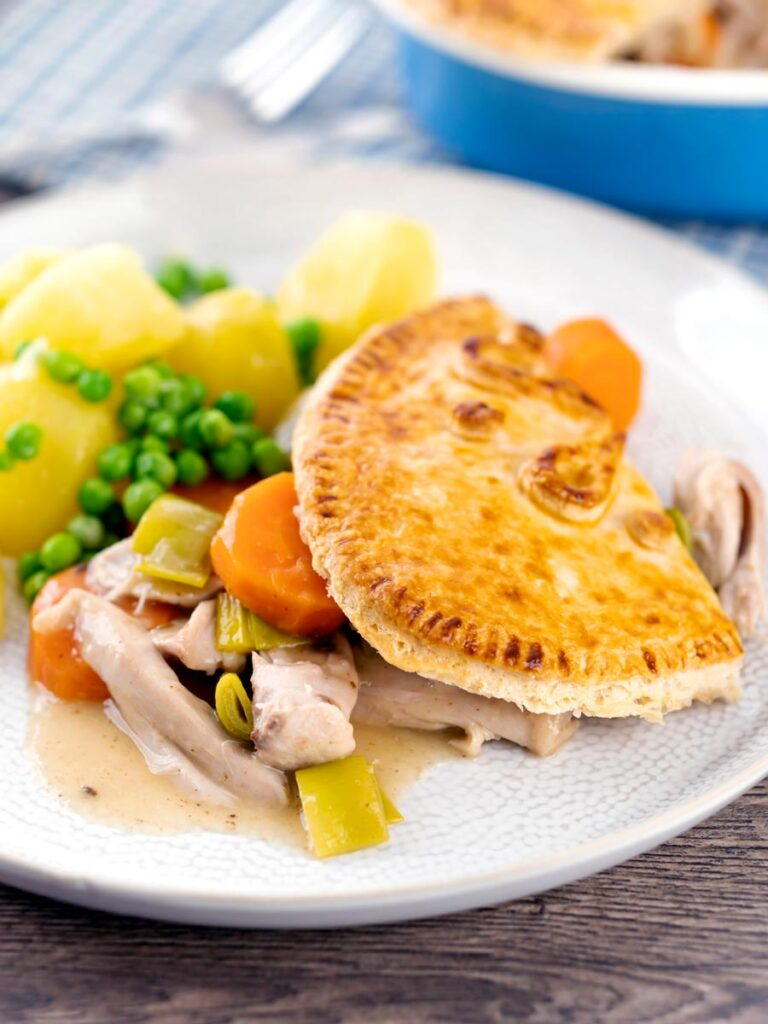 Portrait image of a rabbit pie under a suet crust served on a plate with buttered potatoes and peas