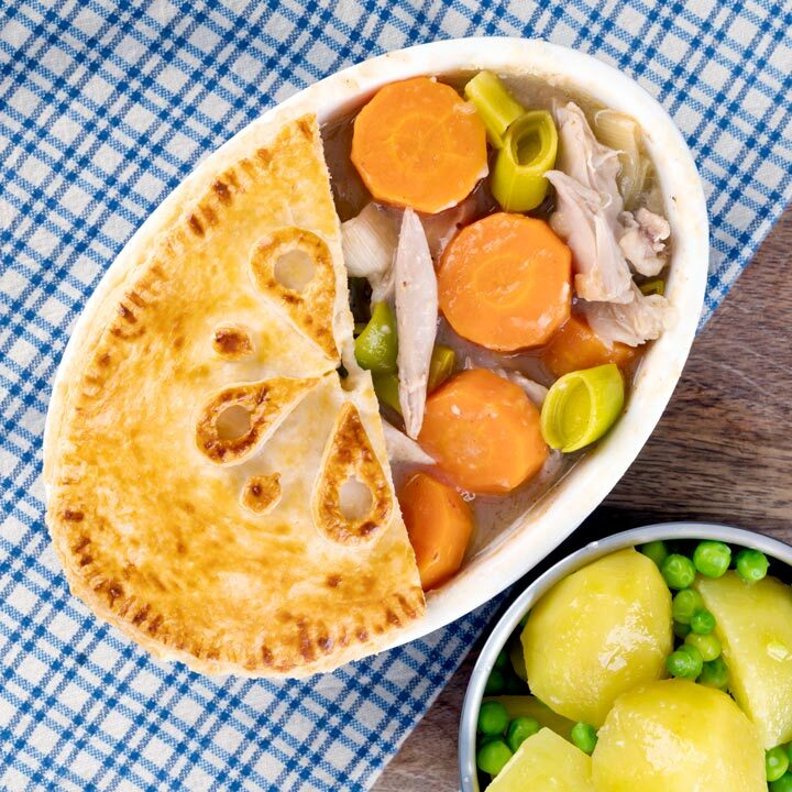 Square overhead image of a rabbit pie under a suet crust lid with half removed to show the filling served alongside a pan of buttered potatoes and peas