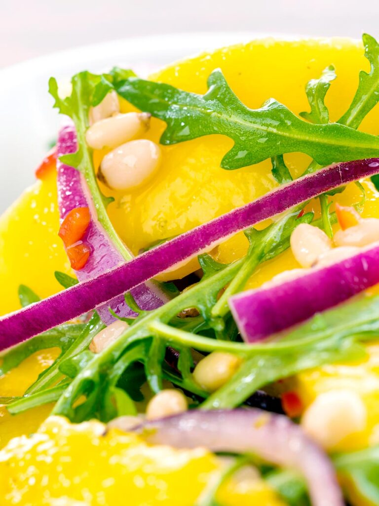 Close up spicy mango salad with rocket or arugula, shredded red onions and pine nuts.