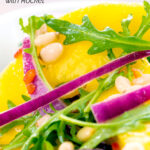 Portrait close up image of a spicy mango salad with rocket or arugula, shredded red onions and pine nuts featuring a title overlay
