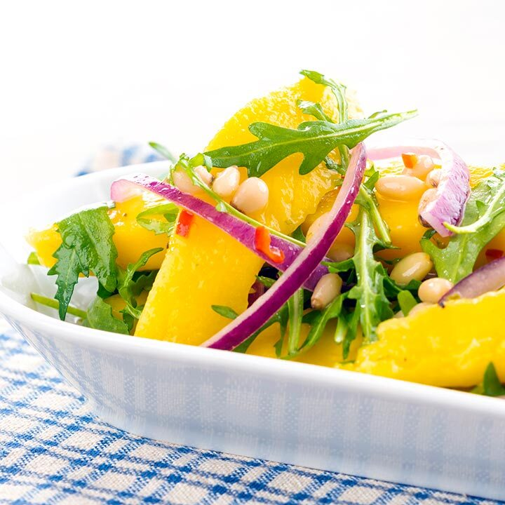 Square image of a spicy mango salad with rocket or arugula, shredded red onions and pine nuts